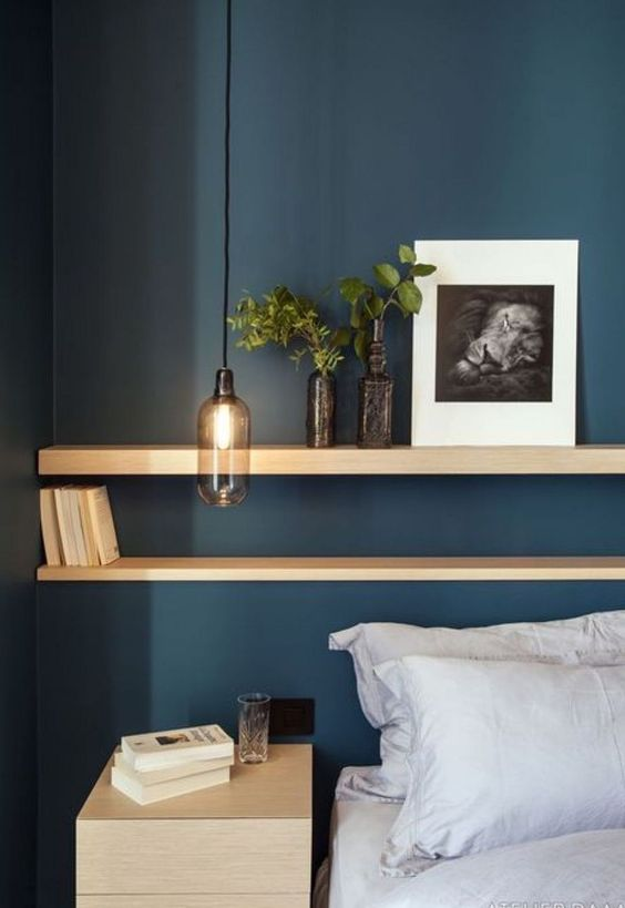 bedroom, dark blue wall, long floating wooden shelves, wooden cabinet, white bedding, clear glass pendant
