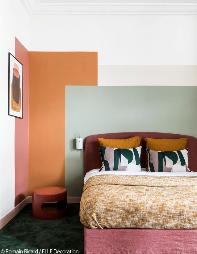 bedroom, green rug, pink bed platform, grey, orang pink painted on the white wall, pink low stool