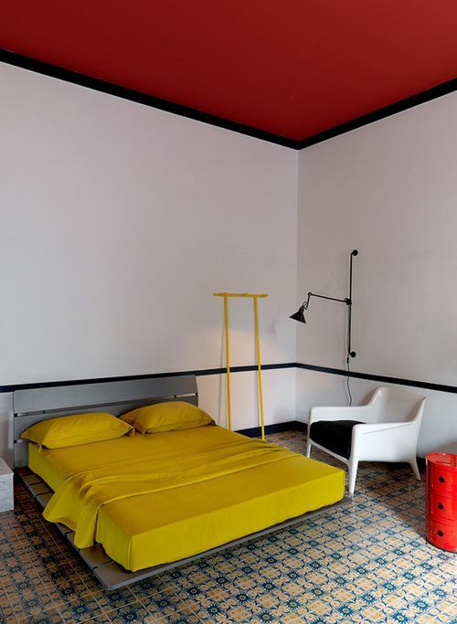 bedroom, patterned floor, white wall, grey bed platform, yellow bedding, red ceiling