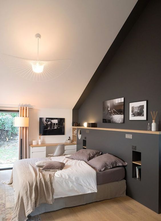bedroom, sloping ceiling, grey statement wall with indented part for shelves, shelves hole in the middle, wooden floor, large pendant
