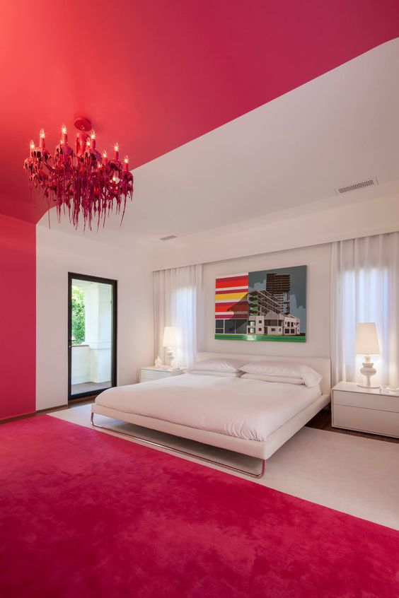 bedroom, white painted bed area, bright pink on the rest, bright pink chnadelier, white side table, white table lamp
