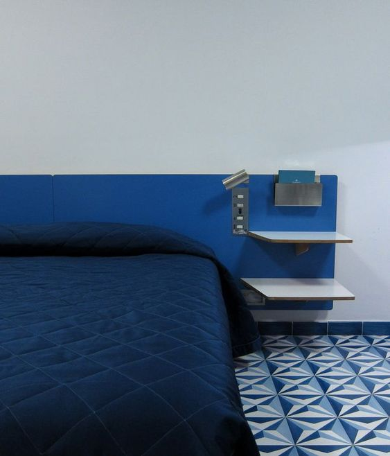 bedroom, white wall, blue painted area on bed head, blue patterned floor, blue bedding