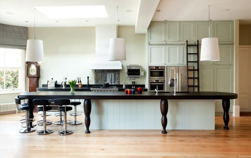 big kitchen islands green cabinets wooden floor black barstools black contertops bigwhite pendant lamps range hood stovetop sink ladder