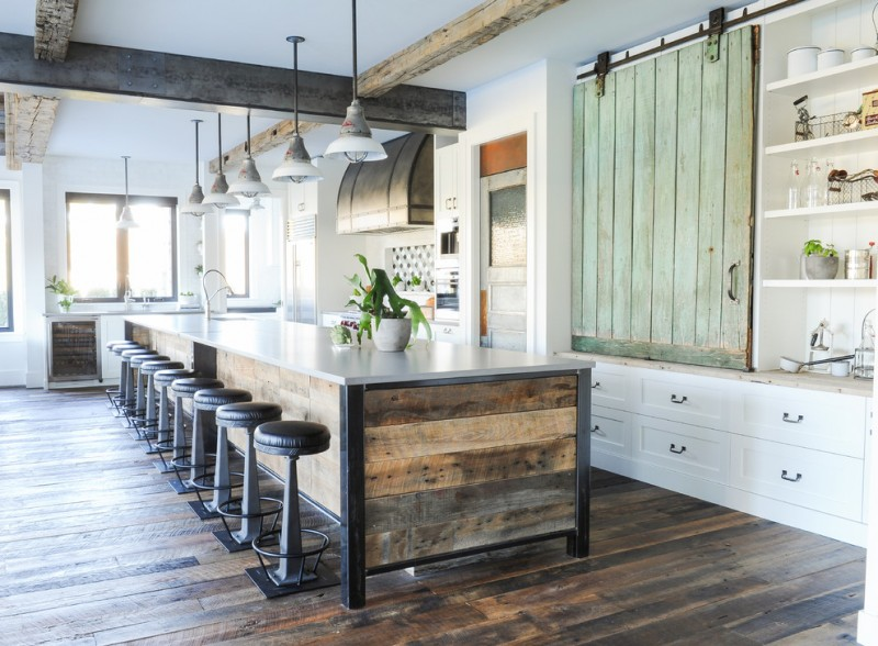 big kitchen islands reclaimed wood island white countertop black barstools wooden floor white cabinets pendant lamps wine fridge sink stovetop shelves
