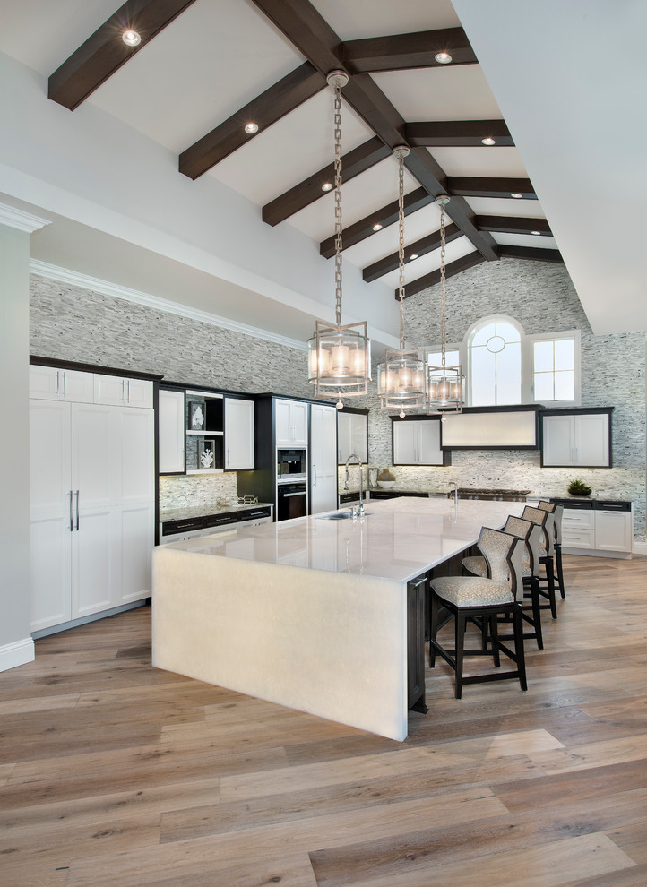 big kitchen islands vaulted ceiling wooden floor lamp white countertops white cabinets barstools glass pendant lamps window stovetop shelves sink