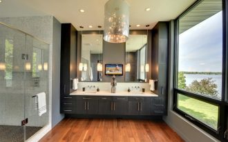 black bathroom cabinets chandelier wall mirrors glass pendant lamps wooden floor white top sinks windows glass shower doors