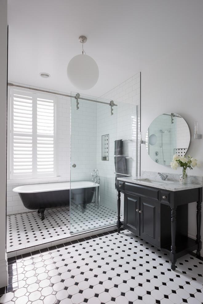 black bathroom cabinets white chandelier black and white mosaic floor tile black freestanding tub towel holder round wall mirror sliding glass door sink window wall sconces