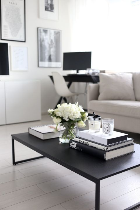 black coffee table, white wooden floor, white wall, white ofa, black study table