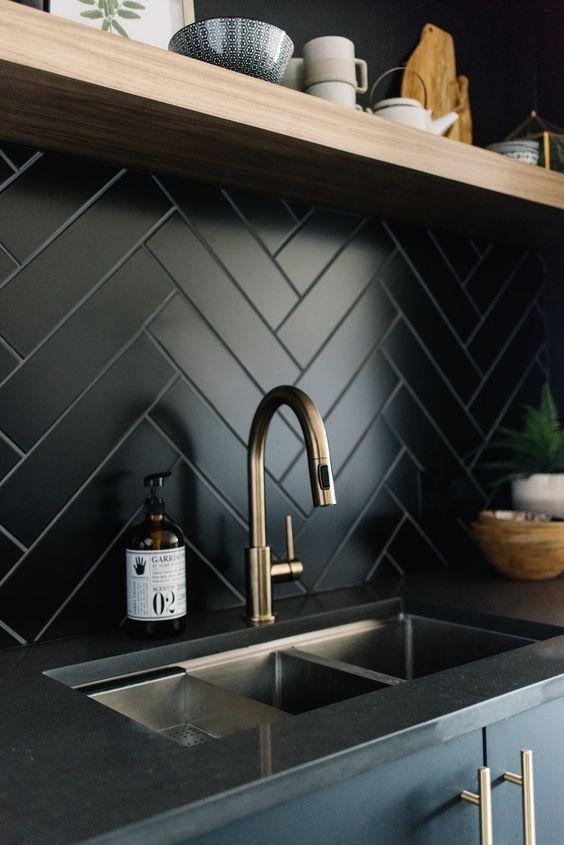 black herringbone backsplash tiles, wooden floating shelves, black top, black cabinet with golden handler