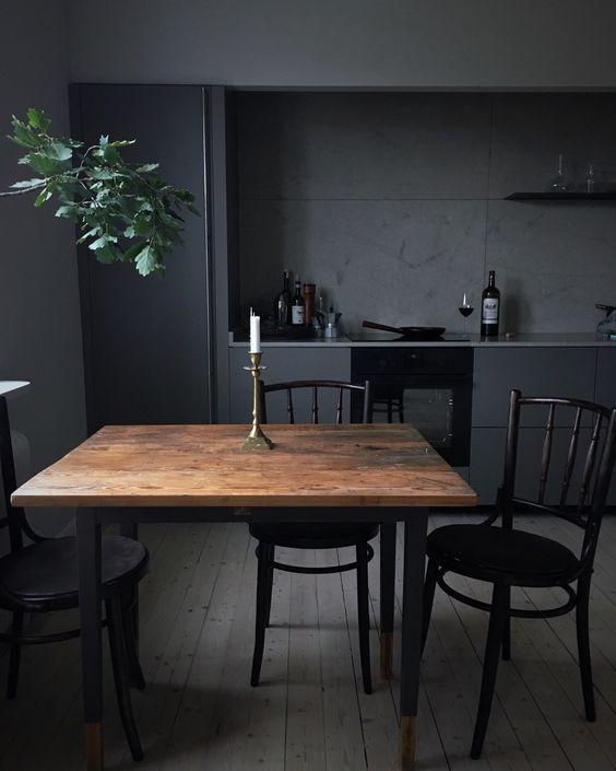 black kitchen, dak wooden floor, black cabinet, dark grey wall, black wooden chairs, wooden table