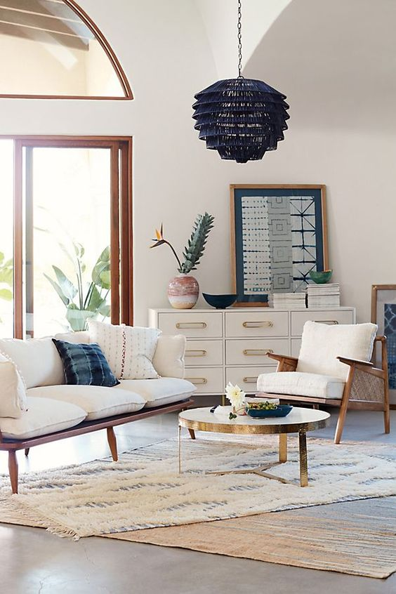 black rattan pendant, seamless floor, white wall, wooden rattan sofa and chairs with white cushions, white cabinet