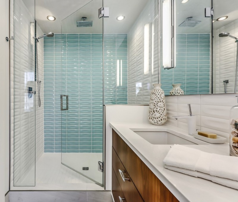 blue wall tile shower fixture glass shower door wooden vanity white op white undermount sin white floor tile white faucet wall mirror wall sconce