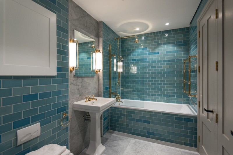 blue wall tile wall sconces gold light fixtures built in bathtub white freestanding sink wall mirror toilet towel holder gray accent wall towel ring