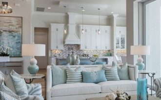 branch pendant on white ceiling, white rug, white sofa, blue white chairs, coffee table, white table lamp