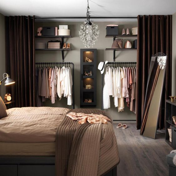 closet behind curtain in bedroom, black wooden floating shelves, black rail to hang clothes, black cabinet, crystal chandelier