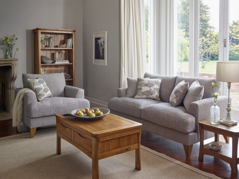 coffee table with storage drawers brown area rug window white curtains pillows throw gray sofa gray armchair woode shelves