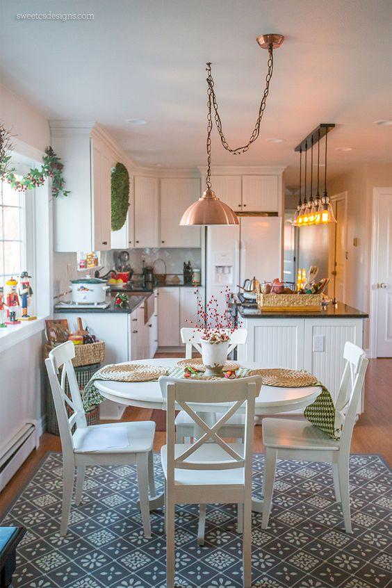 copper pendant, wooden floor, white wooden cabinet, white wooden island, black top, white ceiling, white wooden round table, white wooden chairs, blue rug