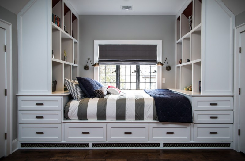 custom kids bed gray window shade windows wall sconces gray and white striped bed cover blue duvet blue pillows white drawers white built in shelves wooden floor