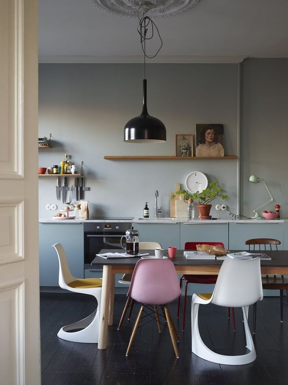 dining room, dark wooden floor, wooden table, white modern designed chair, grey wall, grey floating, wooden floating chelves, black pendant, different chairs