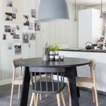 Dining Room, Grey Floor, Grey Round Wooden Dining Table, Wooden Chairs, White Wooden Wall, White Wall, Grey Pendant, White Island With Black Kitchen Top