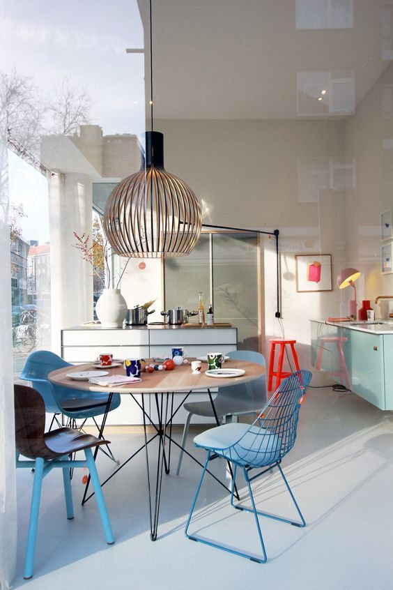 dining room, white floor, white wall, blue different chairs, wooden round table, wooden pendant, white island, blue floating cabinets