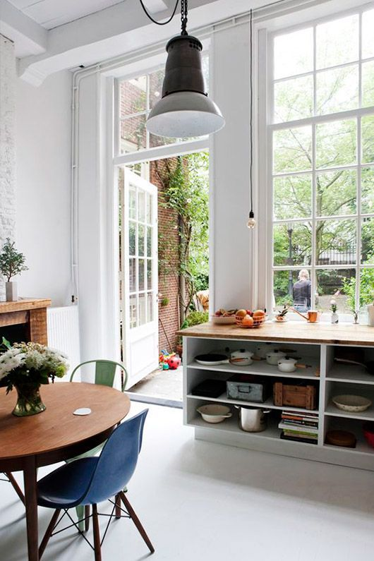 dining room, white floor, white wall, white pendant, wooden round table, modern chairs, wooden chelves, tall glass window, glass door