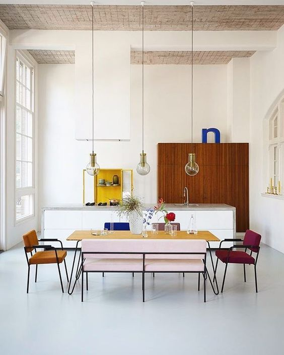 dining room, white floor, white wall, wooden ceiling, glass pendants, yellow long rectangular table, colorful chairs and sofa, tall window
