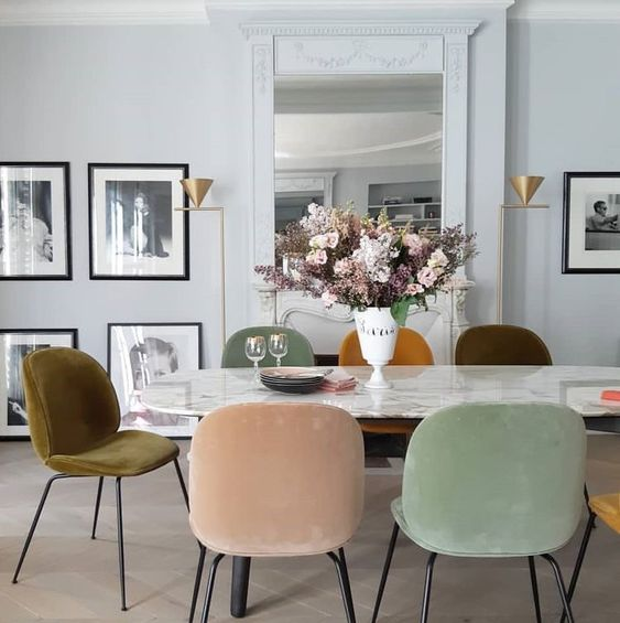 dining room, white marble table, soft colored velvety chairs, white wall, mirror, white fireplace, off white floor
