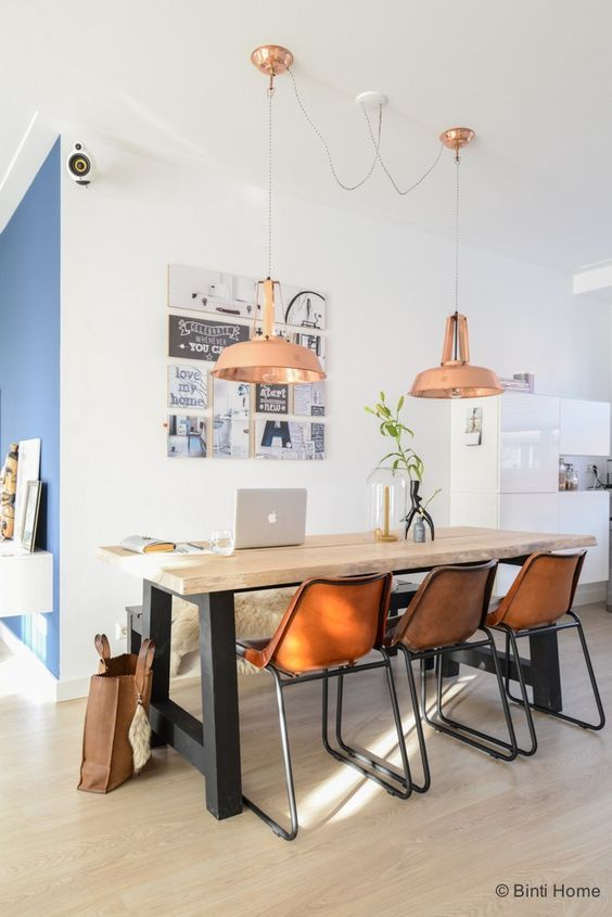 dining room, wooden floor, white wall, blue wall, copper pendants, wooden top table wth black legs, black bench, brown modenr chairs