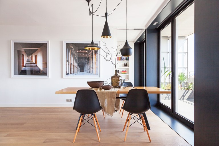 dining room, wooden floor, white wall, white ceiling, glass window with black frame, black pendants with golden inside, wooden table with black modern chairs