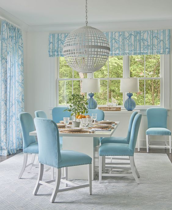 dining set with blue chairs, white square table, grey rug, wooden floor, blue curtain, blue table lamp, white side table, white globe framed pendant