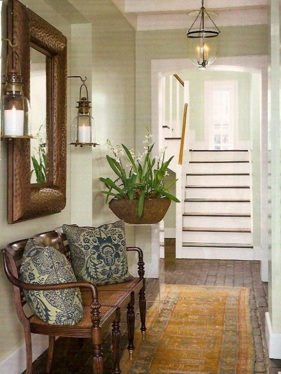 entrance, wooden floor, yellow rug, white painted wall, wooden bench with details, candle sconces, glass chandelier, plants