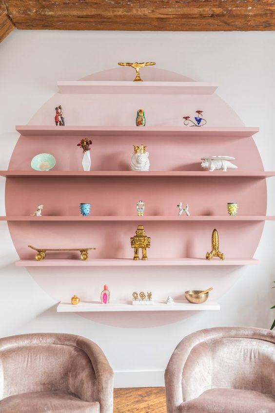 floating shelves with pink obre color ont he shelves and wall