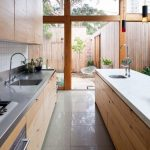 Galley Kitchen, Grey Floor Tiles, Wooden Cabinet, White Top, Stainless Steel Top, White Tiles Backplash, White Ceiling, Clear Glass Wall, Wooden Beams On The Wall