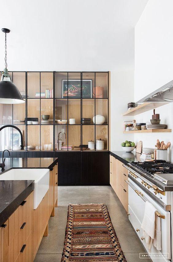galley kitchen, grey seamless floor, wooden bottom cabinet with black top, black built in cupboard with glass door, black pendant, wooden floating shelves
