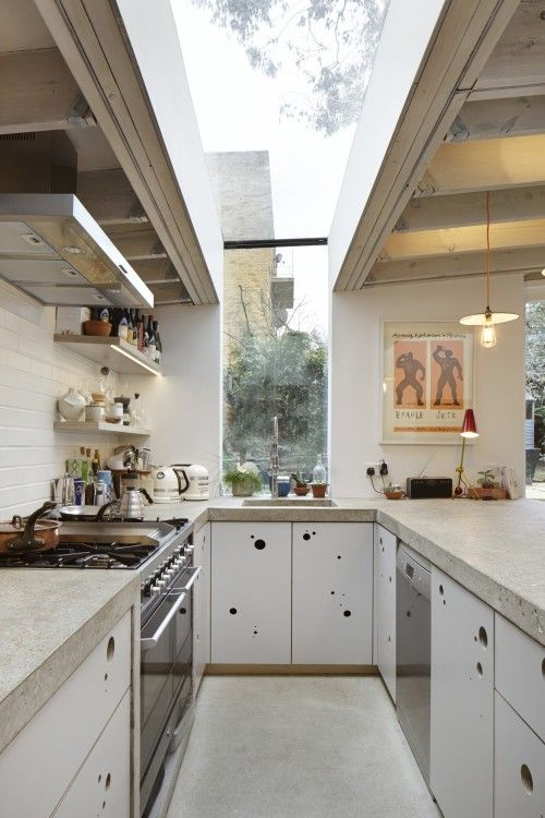 galley kitchen, white floor, white bottom cabinet with hole handler, beige marble top, white plank wall, floating open shelves, glass ceiling and wall
