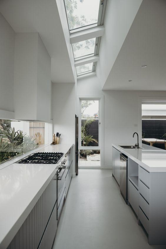 galley kitchen, white seamless floor, white wall, white ceiling, clear glass ceiling, clear glass backsplash, grey bottom cabinet, shelves