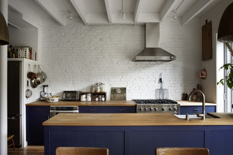 galley kitchen, wooden floor, dark royal blue bottom cabinet with wooden top, farmhouse sink, white wall, hood,