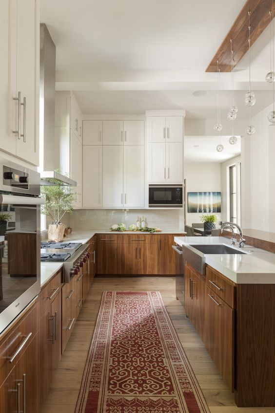galley kitchen, wooden floor, white upper kitchen, brown wooden bottom kitchen with white top, wooden board for clear ball pendants