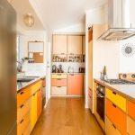Galley Kitchen, Wooden Floor, White Wall, Yellow Orange Brown Cabinet Blocks, Steel Ktchen Top, Pendant, Steel Hood