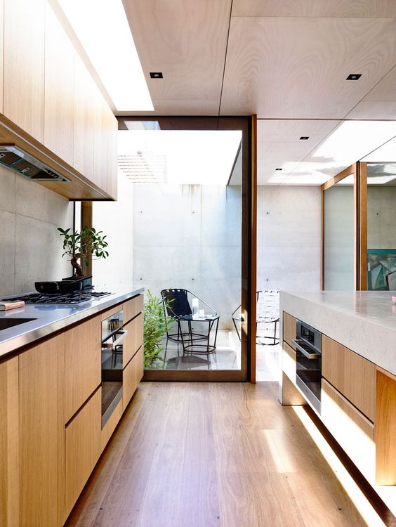 galley kitchen, wooden floor, wooden bottom cabinet, white marble top, stainless steel top, marble backsplash, wooden upper cabinet, wooden ceiling, glass partition