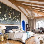 Giant Wall Art Chandelier Wood Beams Blue Tufted Headboard Bed Mediterranean Rug Nightstands Table Lamps Wooden Shelves Window Beige Curtains