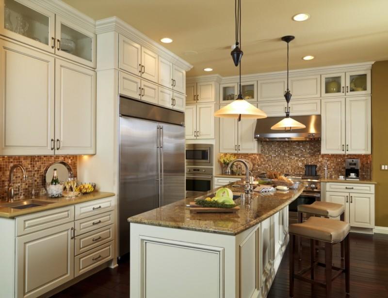 glass mosaic backsplash beige granite countertops white cabinets white island stools dink faucet pendant lamps refrigerator stovetop rangehood