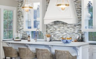 glass mosaic backsplash glass and gold pendant lamps white cabinets white island barstools wooden floor glass shelves stovetop white rangehood