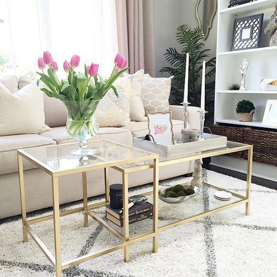 glass nesting table with golden frame and legs, white rug, white sofa, white shelves