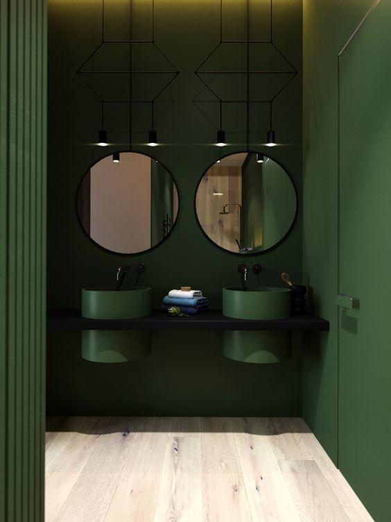 green bathroom, green wall, black vanity, green round sink, round mirror, black wired pendant, wooden floor