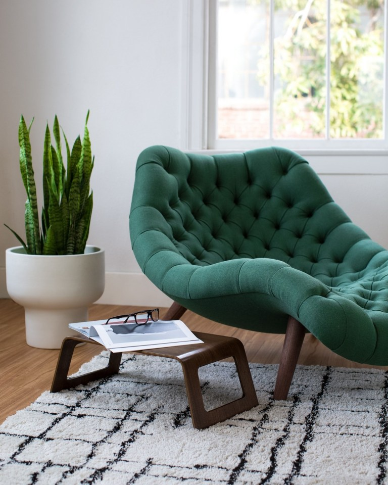 green tufted lounge chair with wooden legs, wooden stool, white rug, wooden floor, white pot