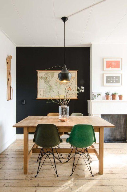 green yellows grey mid century modern chair, wooden table, wooden floor, black statement wall, black pendant