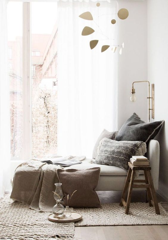 grey lounge chair near the window, rattan rug, sconce, wooden stool, wooden floor