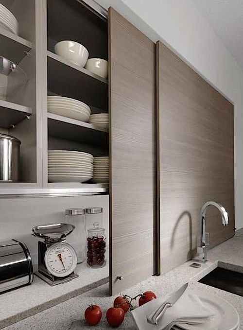 high end kitchen storage with sliding doors on the marble kitchen top, shelves inside, sink